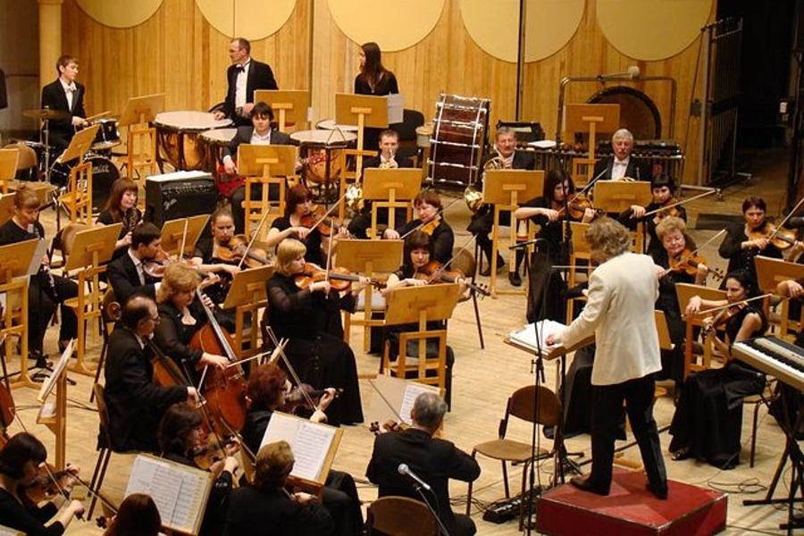 Na zdjęciu widać orkiestrę symfoniczną i dyrygenta za pulpitem dyrygenckim.