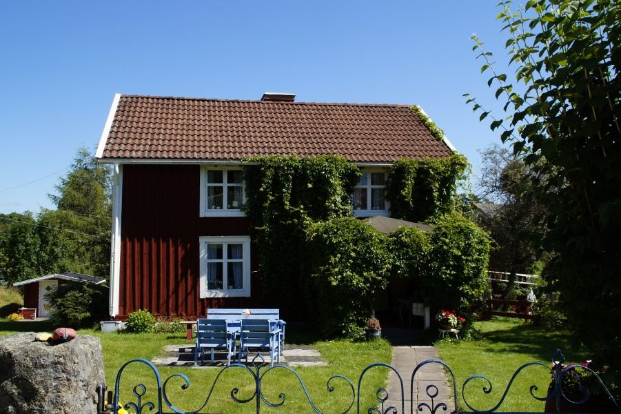 Czerwono-brązowy dom jednopiętrowy na tle błękitnego nieba, z czerwonym dachem i białymi oknami, z zielonym podwórzem na którym stoją niebieskie meble ogrodowe