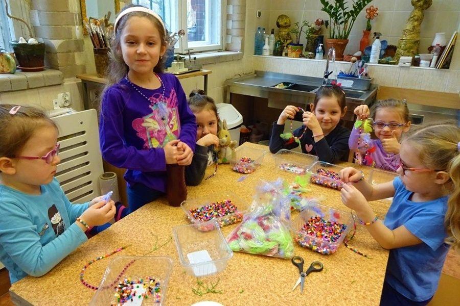 Grupa dziewcząt kolorowo ubranych siedzi przy stole i nawleka kolorowe koraliki i piórka tworząc biżuterię.
