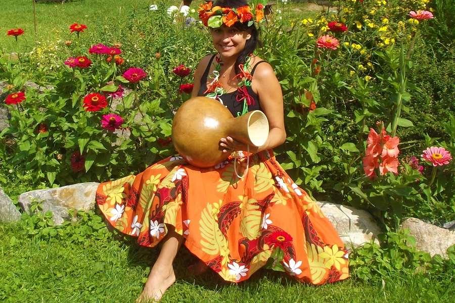 Kobieta z pomarańczowym wiankiem na głowie i w pomarańczowej spódnicy w kwiaty siedzi na trawie trzymając tykwę w dłoniach.