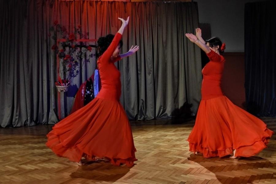 Dwie kobiety ubrane w czerwone suknie stoją w tanecznej pozie z jedną ręką u góry, przodem do siebie.