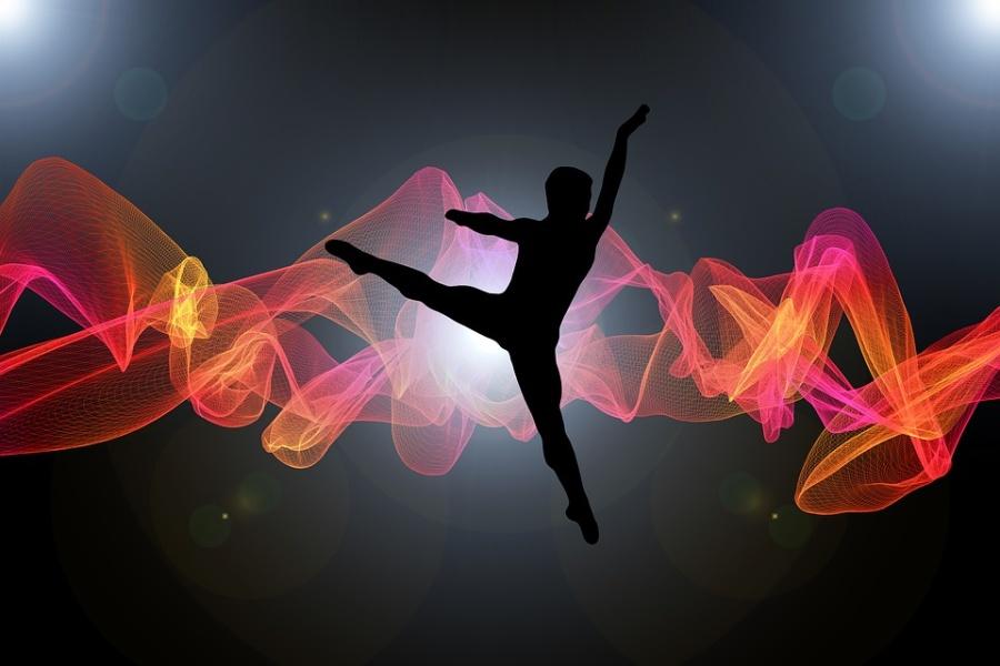 Zdjęcie przedstawia skok tancerza w powietrzu na tle pofalowanej tkaniny o barwie różowo –pomarańczowej.