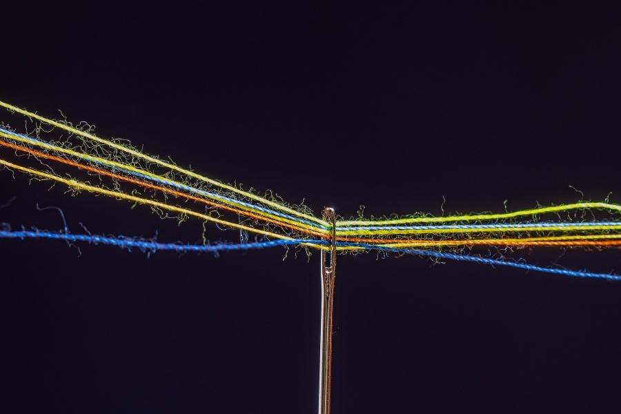Igła krawiecka przez której ucho przechodzi kilka różnobarwnych nici