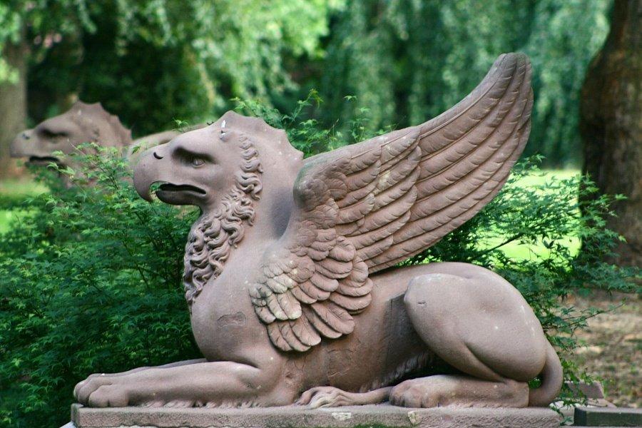 Szary kamienny posąg gryfa z lekko uniesionymi skrzydłami widziany z profilu na tle zielonego parku oraz rozmazanego posągu drugiego gryfa