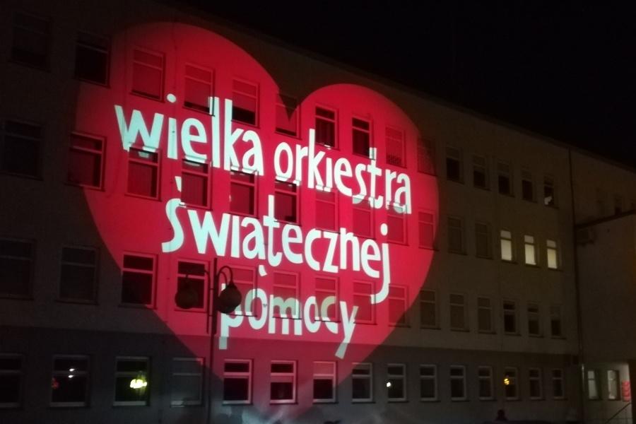 """Napis """"Wielka Orkiestra Świątecznej Pomocy"""" wyświetlony na fasadzie budynku"""