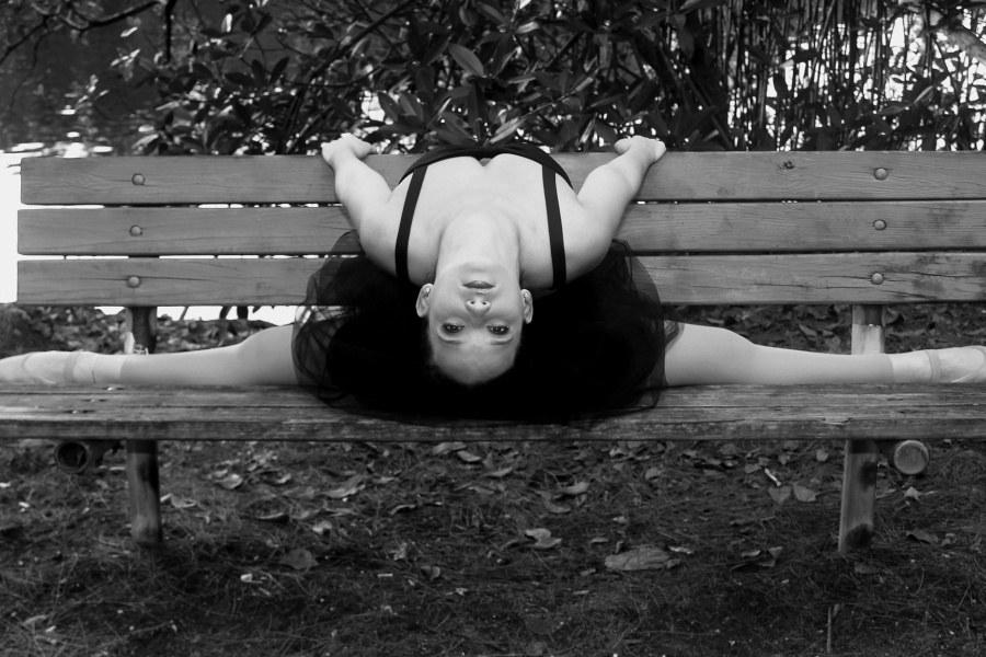 baletnica siedząca na ławce w szpagacie tureckim w wygięciu tyłem