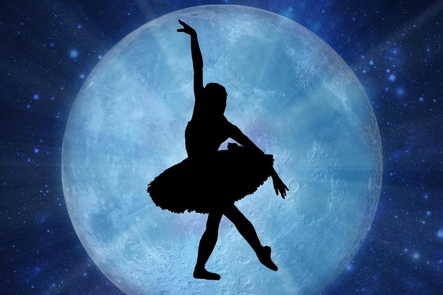 Zdjęcie przedstawia pozę tancerki przy pełni księżyca w kolorystyce błękitu