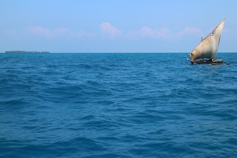 Zdjęcie przedstawia łódź z rozwiniętym żaglem na pełnym morzu