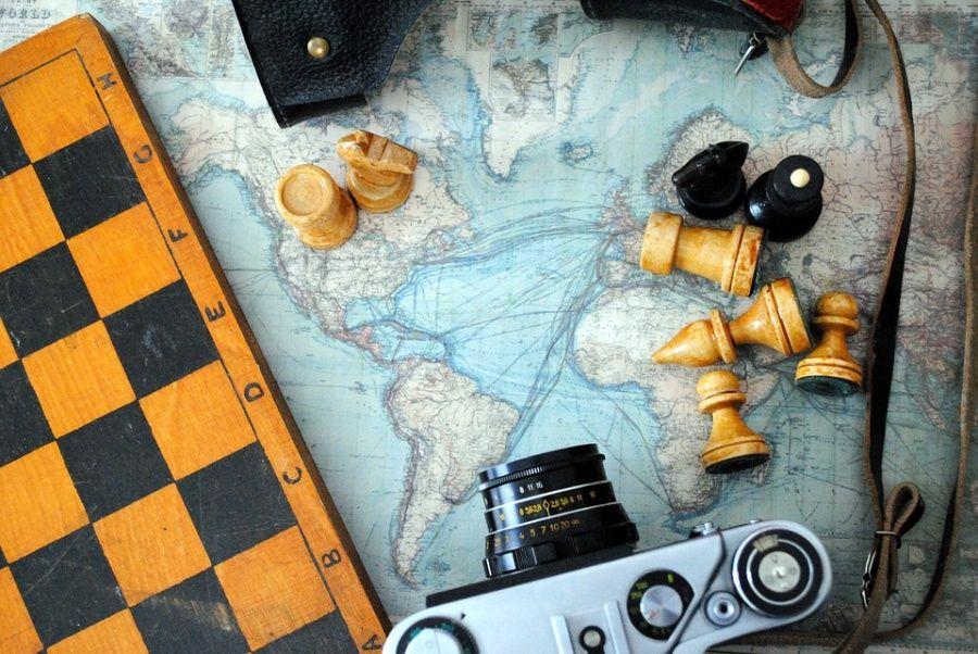 na zdjeciu widoczny aparat fotograficzny, fragment szachownicy i rozsypane pionki leżace na mapie świata