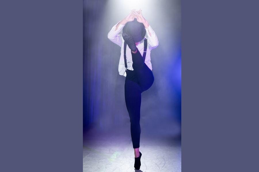 kobieta w kapeluszu tańczy ukrywajac twarz