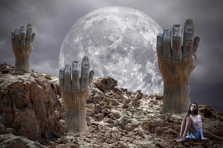 widać na pierwszym planie szarą kamienistą przestrzeń, z której wyrastają drewniane dłonie, w prawym dolnym rogu siedzi dziewczyna, w oddali jest szaroniebieskie niebo i duży okrągły księżyc