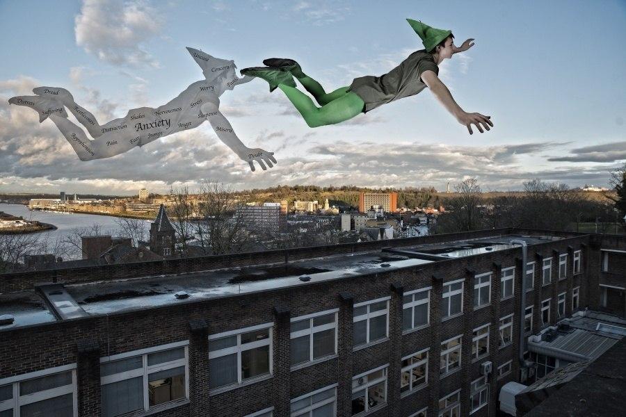 Zdjęcie przedstawia Piotrusia Pana lecącego nad budynkiem.
