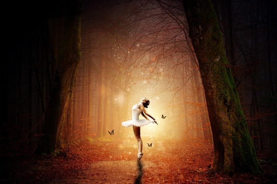 Zdjęcie przedstawia oświetloną baletnicę otoczoną motylami w samym środku lasu.