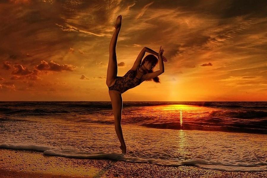 Zdjęcie przedstawia ćwiczącą dziewczynę na plaży przy zachodzie słońca