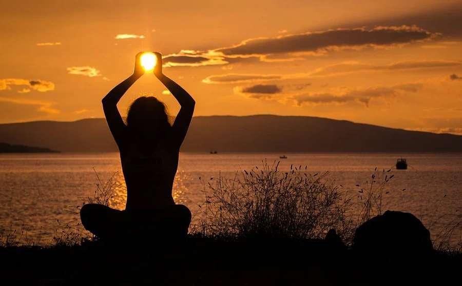 Zdjęcie przedstawia zachód słońca i postać kobiety w pozycji siedzącej z nogami ułożonymi po turecku, ręce znajdują się w górze nad głową - iluzja trzymania słońca w dłoniach