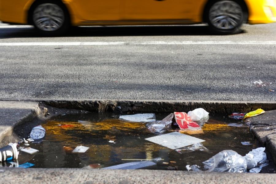 Zdjęcie przedstawia ulicę, na której leżą rozsypane śmieci w kałuży wody.