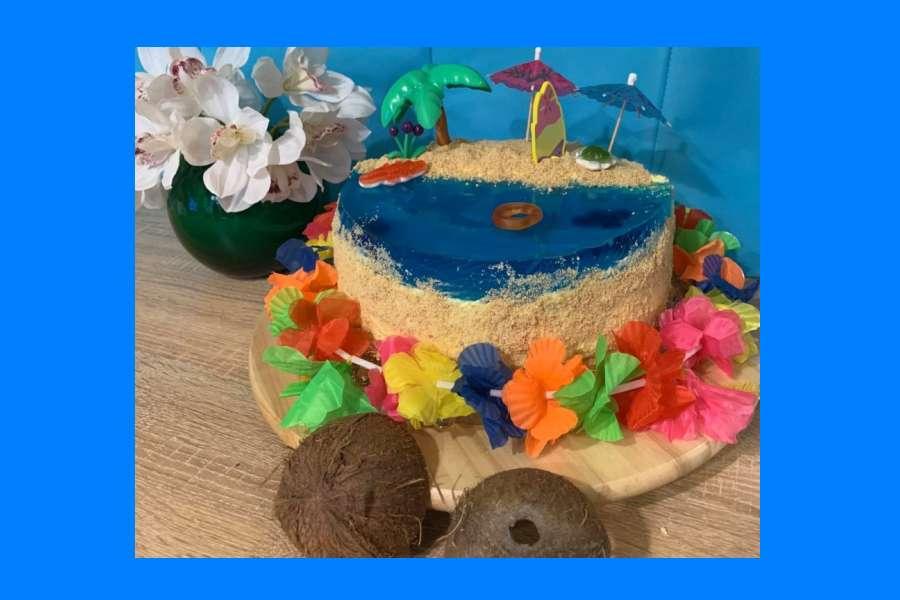 tort w kolorze niebiesko-beżowym, z hawajskimi ozdobami (kwiatami wokół) oraz palmą i parasolkami.