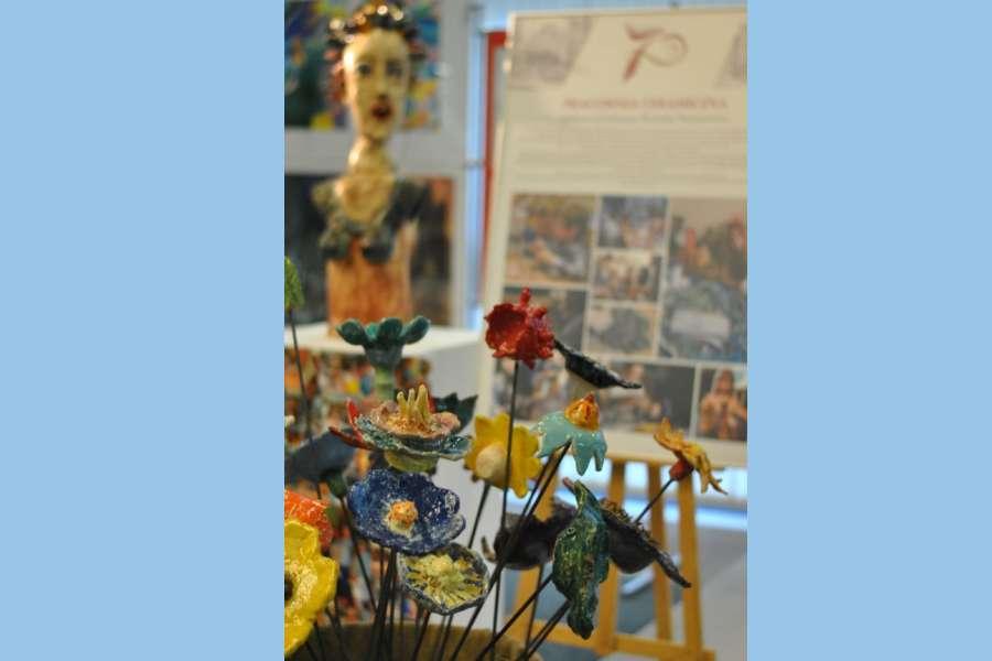 Ceramiczne kwiaty na nieostrym tle ceramicznej rzeźby i afiszu.