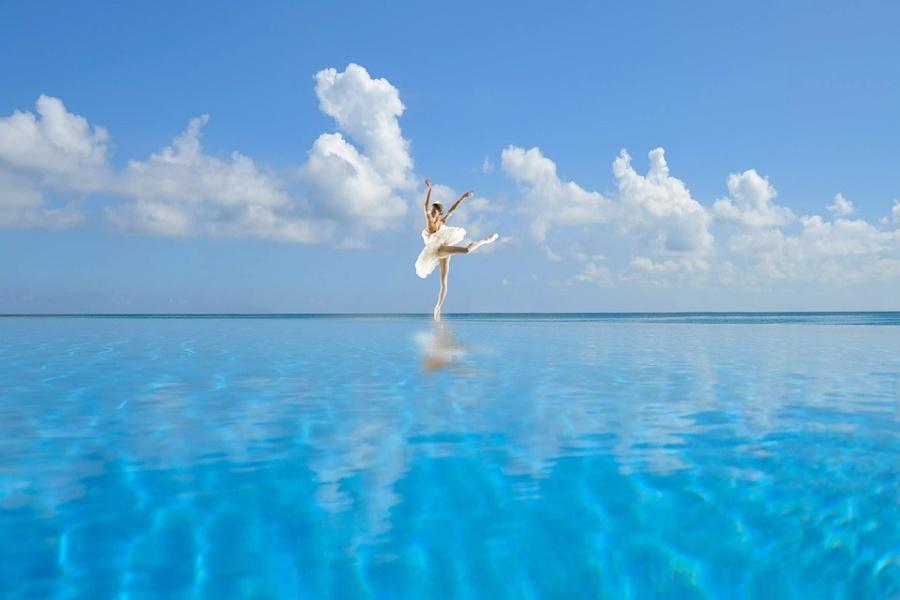 Zdjęcie przedstawia baletnicę stojącą na pointach w środku oceanu w pozycji arabesque.