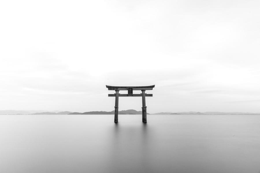Japońska brama Tori na tle stalowego nieba i stojąca w jeziorze o szarym kolorze