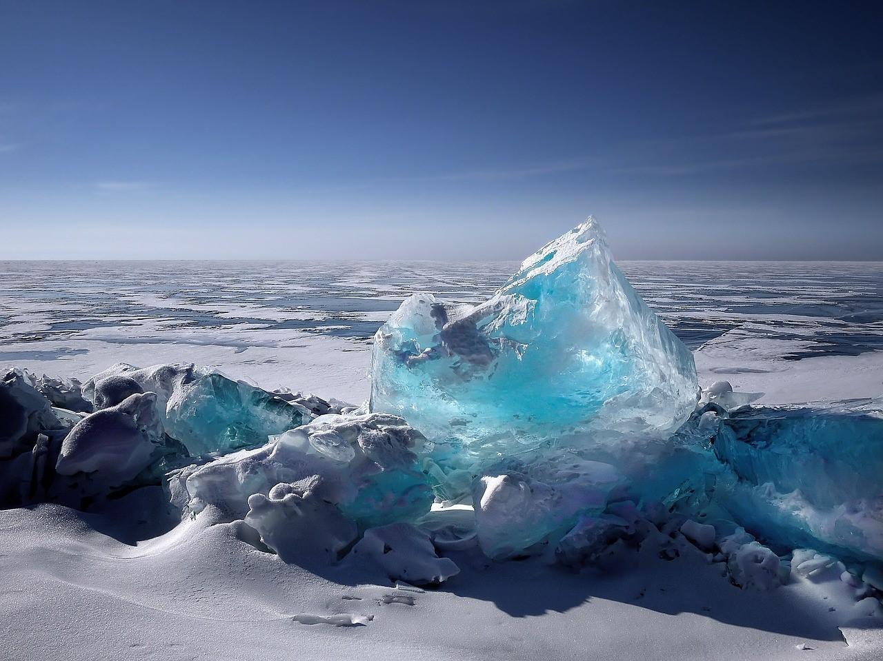 Niebieskawa bryła lodu wystaje zalodzonego akwenu