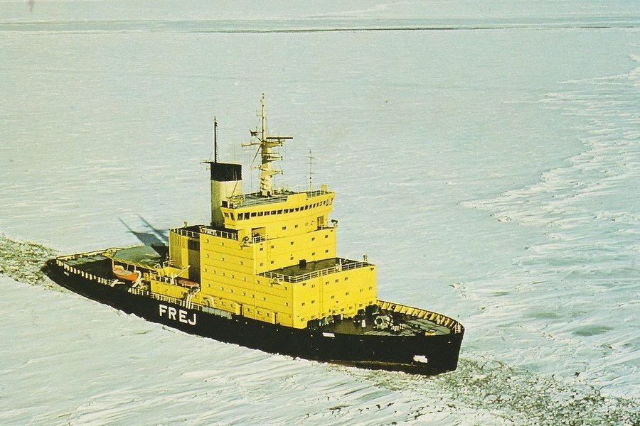 Na białej tafli morza lodołamacz; na czarnym niskim kadłubie wysoka jasnożółta nadbudówka