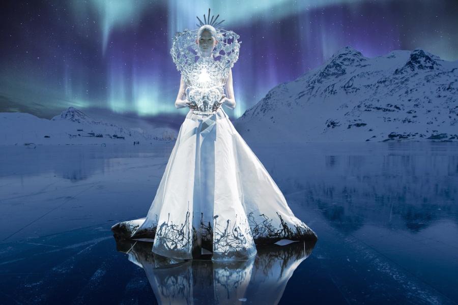 Zdjęcie przedstawia kobietę w bieli na tle zamarzniętego jeziora, gór i zorzy polarnej