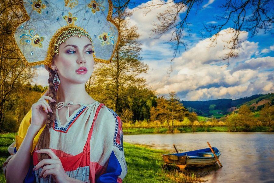 Zdjęcie przedstawia kobietę w ludowym stroju rosyjskim na tle jeziora z zacumowaną łodzią.