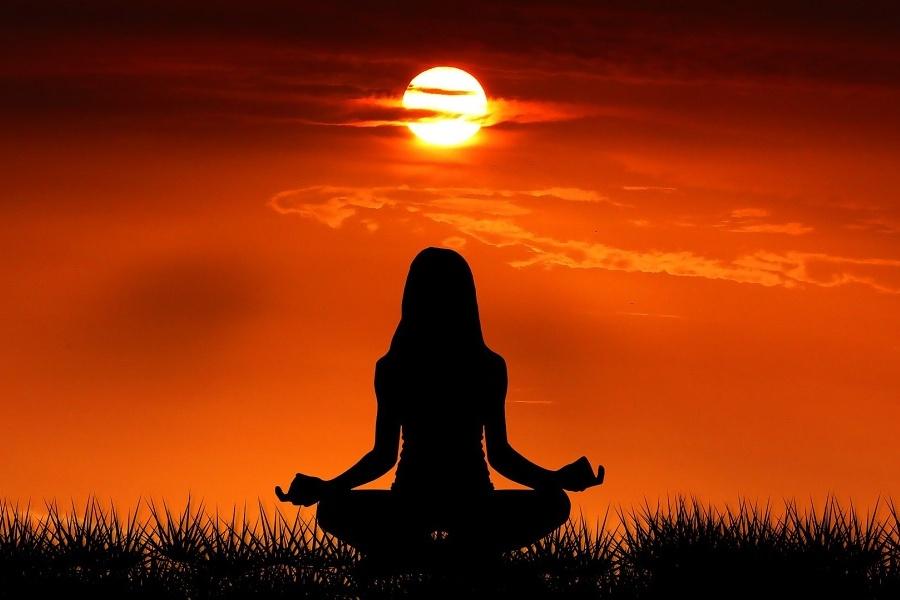 kobieta ćwicząca jogę na tle zachodzącego słońca