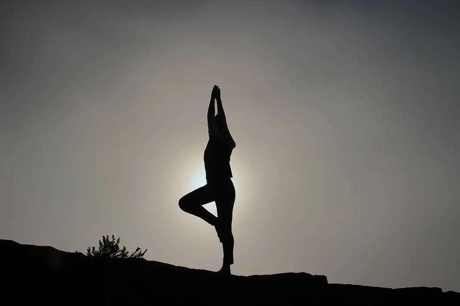Zdjęcie przedstawia sylwetkę osoby praktykującej jogę o zachodzie słońca.