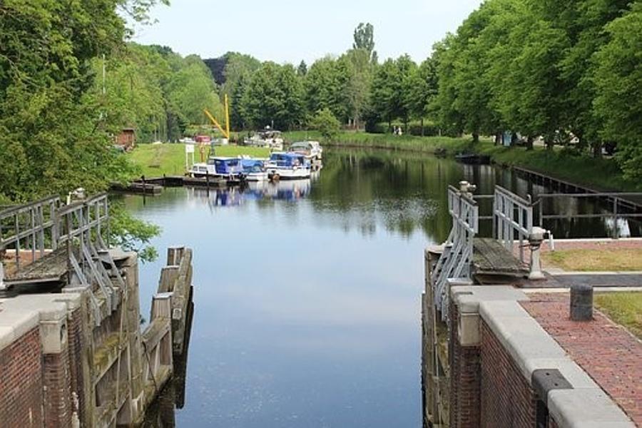 Śluza z wrotami otworzonymi na wody kanału i stojące w oddali łodzie.