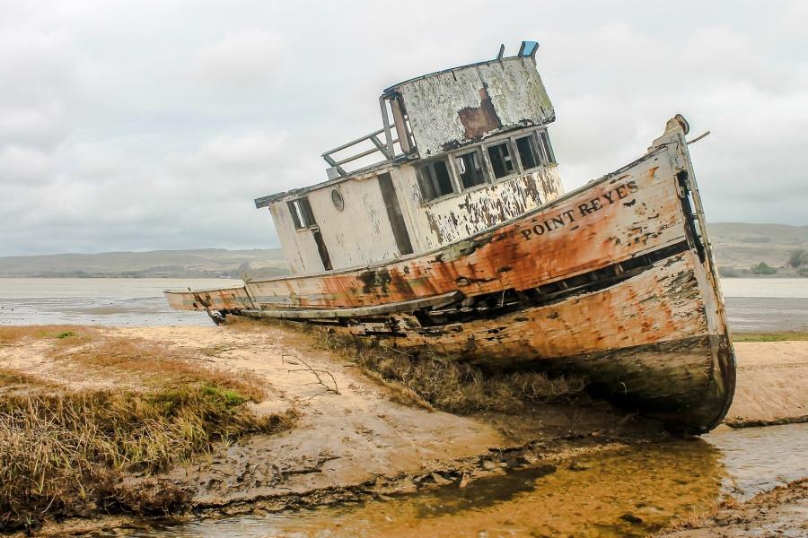 Fragment plaży, na której znajduje wrak starego kutra rybackiego mocno osadzonego w piaszczystym brzegu.