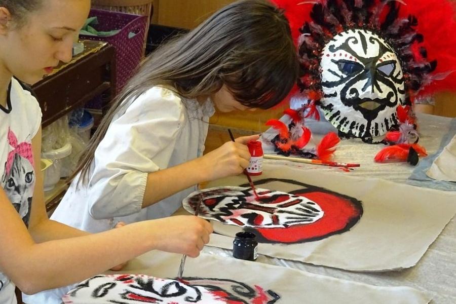 Dwie dziewczynki malujące maski.