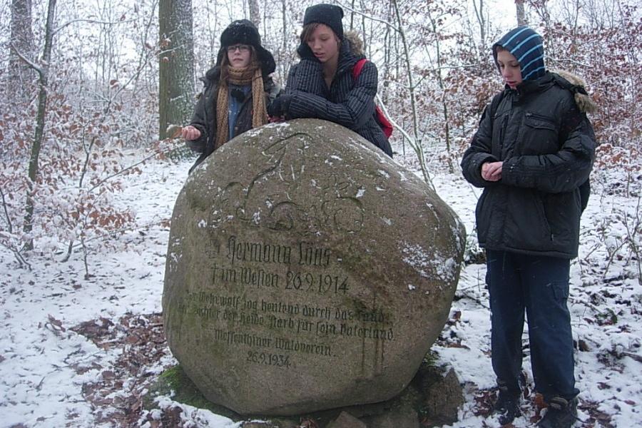 zima, młodzież przy głazie z zajączkami