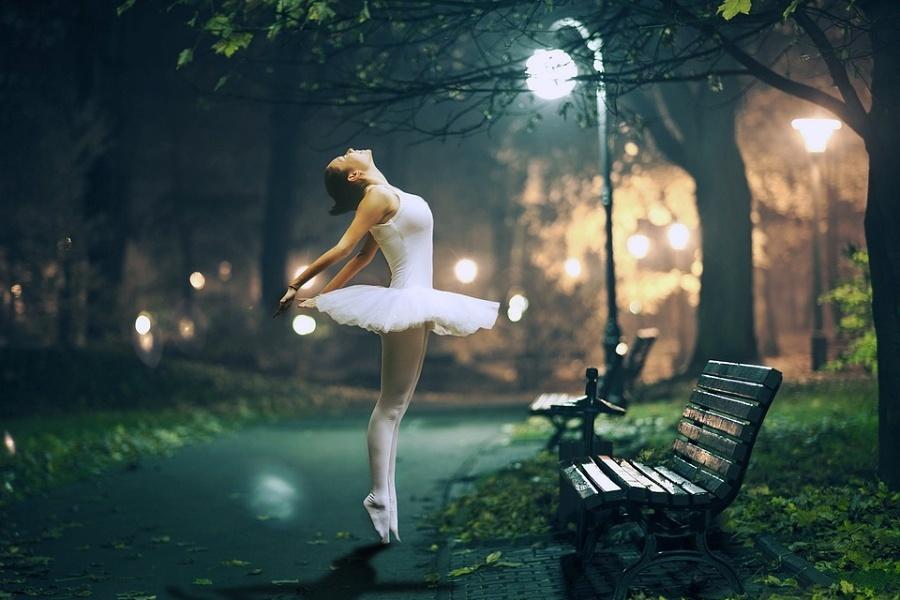 Zdjęcie przedstawia baletnicę w parku przy ławeczce i zapalonej latarni.