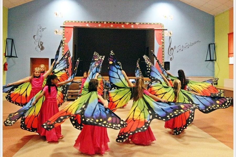 Tańczące w kole dziewczęta ze skrzydłami motyla