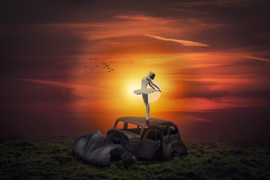 Zdjęcie przedstawia baletnicę stojącą na wraku samochodu przy zachodzie słońca.