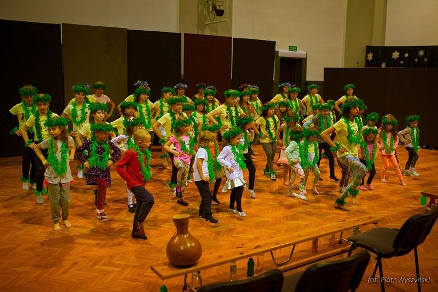 Grupa osób w różnym wieku tańcząca na scenie.