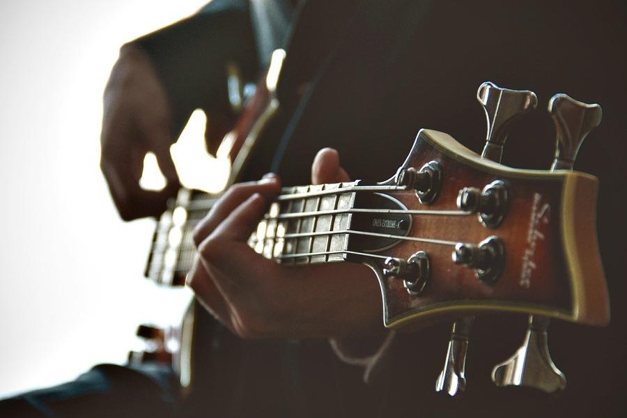 Na zdjęciu widać gitarzystę, który gra na gitarze basowej.