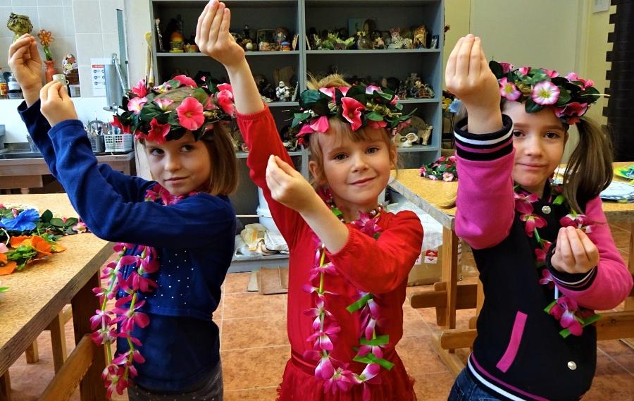 Trzy dziewczynki stoją obok siebie z rękami uniesionymi do góry tworząc z palców dłoni pąk kwiatowy. Mają na głowach wianki , a na szyi girlandy z różowych kwiatów.