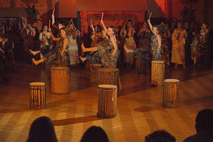 Grupa dziewcząt w zielononiebieskich sukniach tańczy przy bębnach afrykańskich.