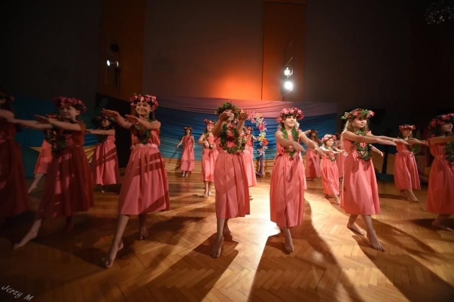 Grupa dziewcząt w różowych sukniach i wiankach na głowach stoi w tanecznej pozie