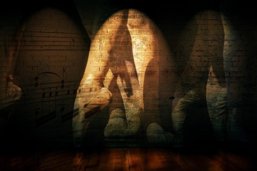 stopy baletnicy w pointach, podświetlonej światłem na tle ściany z cegły ozdobionej nutami na pięciolinii