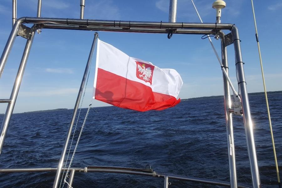 Polska Bandera powiewa na rufie jachtu s/y Dar Szczecina, w tle widać morze