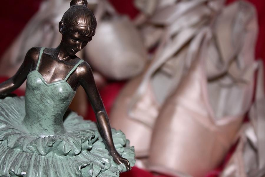 Na pierwszym planie zdjęcia widoczna jest mosiężna figurka baletnicy, tłem są baletki.