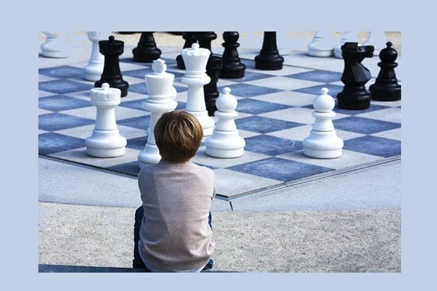 chłopiec siedziący przed wielką szachownicą
