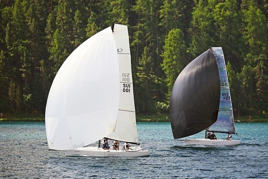 Dwa jachty pod pełnymi żaglami ścigają się na wodach jeziora na tle zalesionego brzegu