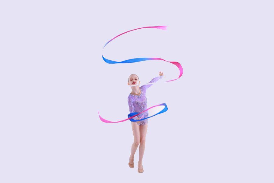 gimnastyczka w fioletowym kostiumie ze wstążką, wykonująca wężyk