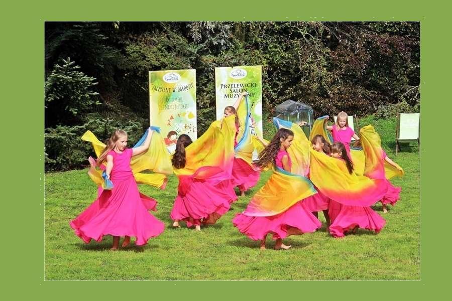 Grupa dziewcząt w różowych sukniach z żółto- różowymi woalami w rękach tańczy na trawie.