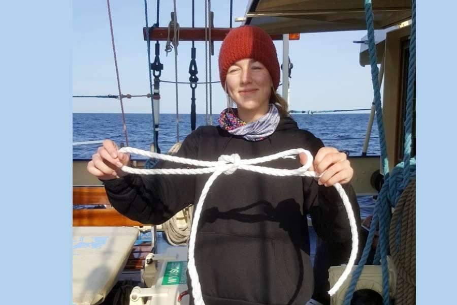 Na pokładzie żaglowca STS KAPITAN BORCHARDT uczennica Karolina trzyma przed sobą białą linkę z zawiązanym węzłem. Za plecami widać spokojne morze.